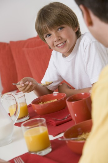 Smiling boy eating breakfast with his father : Stock Photo