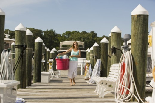 Stock Photo: 1557R-298112 Woman carrying basket of towels on pier