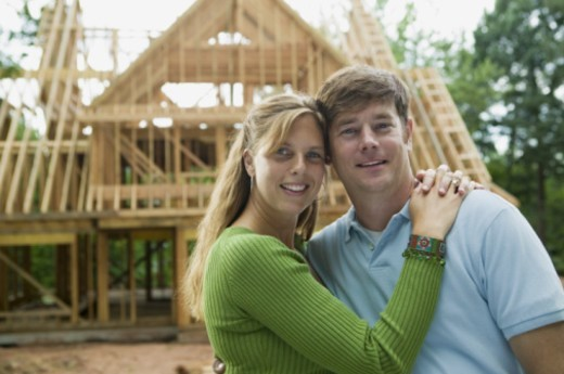 Couple embracing in front of construction site : Stock Photo