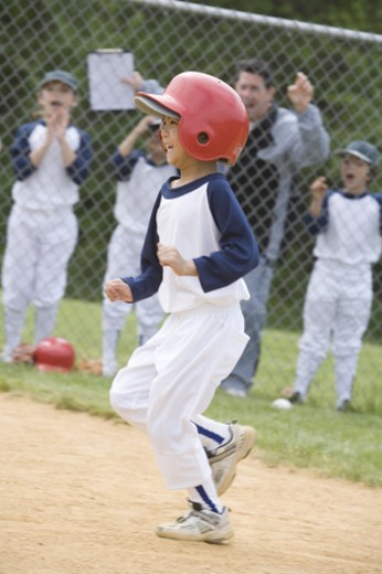 Youth league batter running bases : Stock Photo