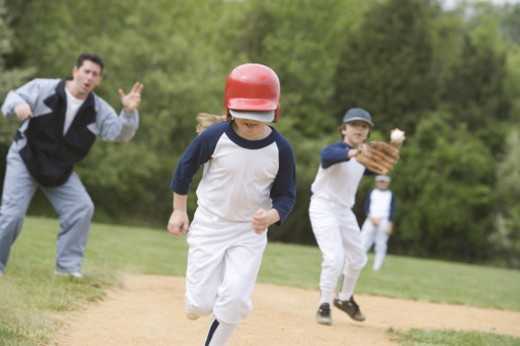 Stock Photo: 1557R-299903 Girl running bases in youth league game