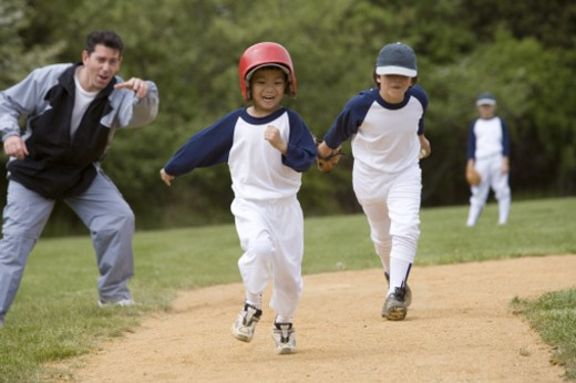 Boy running bases in youth league game : Stock Photo