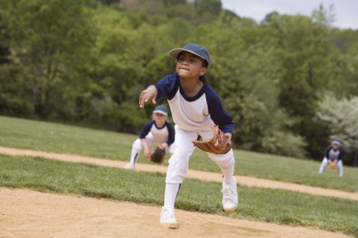 Girl throwing in youth league softball game : Stock Photo