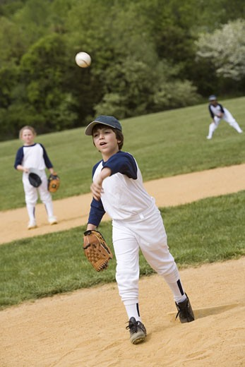 Boy throwing in youth league baseball game : Stock Photo