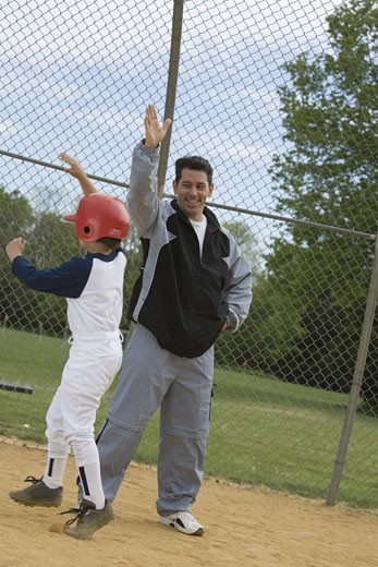 Stock Photo: 1557R-299936 Coach high-fiving youth league batter