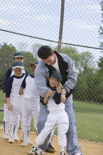 Stock Photo: 1557R-299939 Coach hugging youth league softball player