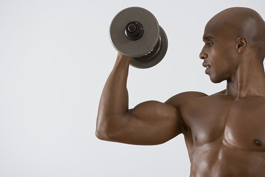 Muscular man lifting dumbbell : Stock Photo
