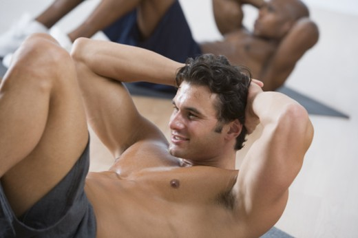 Muscular man doing sit-ups : Stock Photo