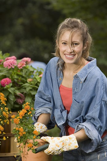 Stock Photo: 1557R-300955 Woman planting flowers in pot