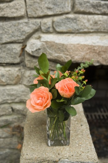 Roses and leaves in glass on stone slab : Stock Photo