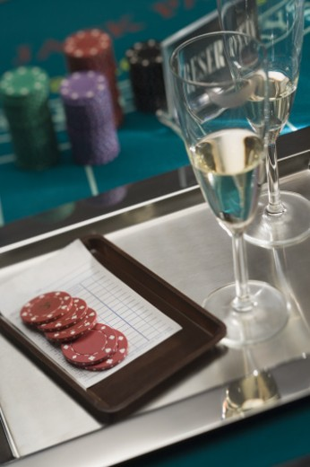 Stock Photo: 1557R-301250 Champagne and bar tab paid in poker chips