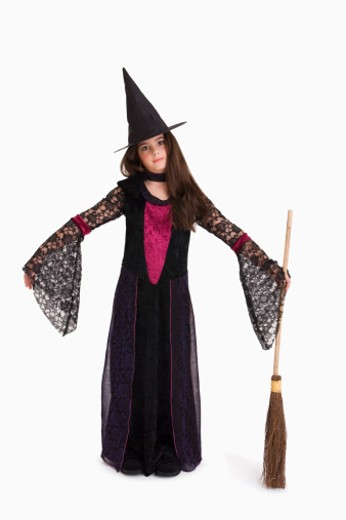 Girl in witch costume with broom : Stock Photo