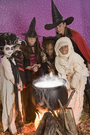 Children and woman in Halloween costumes around cauldron : Stock Photo