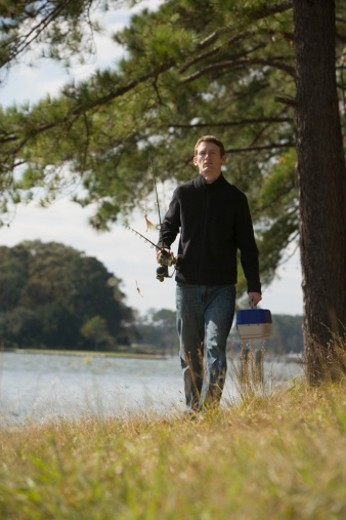 Stock Photo: 1557R-301858 Man walking with fishing tackle