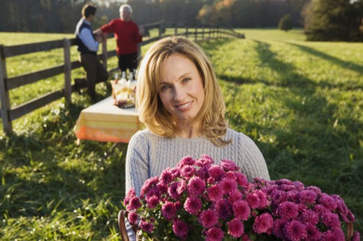 Smiling woman with flowers : Stock Photo