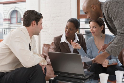 Stock Photo: 1557R-302663 Businesspeople talking over laptop