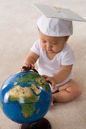 Scholar baby with globe and mortarboard : Stock Photo