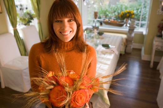 Woman with autumn flower arrangement : Stock Photo