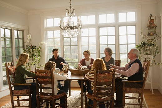 Stock Photo: 1557R-302868 Family sitting around dining room table