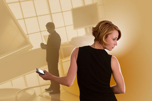 Businesswoman with smartphone looking over shoulder and silhouette of businessman with computer monitors : Stock Photo