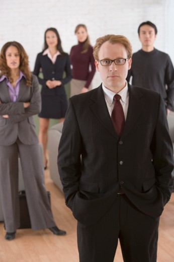Portrait of serious businessman with others : Stock Photo