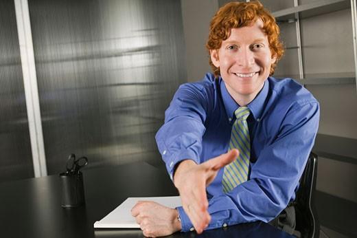 Friendly businessman offering handshake : Stock Photo
