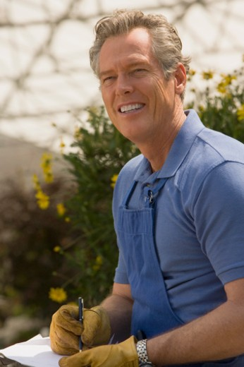 Smiling man working at greenhouse : Stock Photo