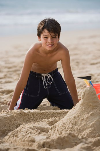 Stock Photo: 1557R-305447 Smiling boy making sand castle at beach
