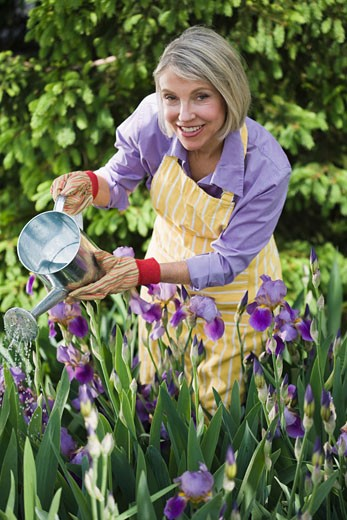 Smiling gardener with watering flowers : Stock Photo