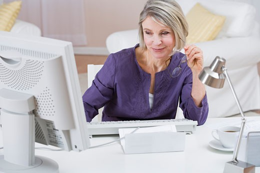 Woman using computer to pay bills : Stock Photo