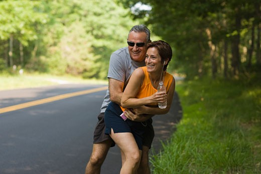 Stock Photo: 1557R-307212 Jogging couple embracing at roadside