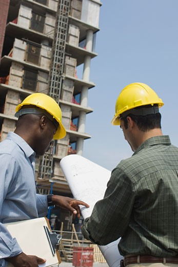 Architects with schematics at construction site : Stock Photo