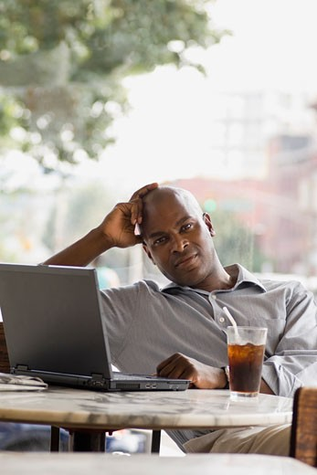 Man using laptop at cafe : Stock Photo