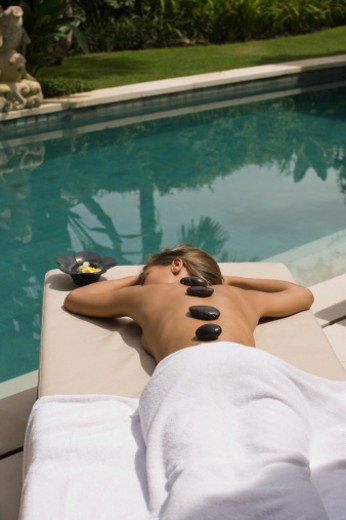Woman having a hot stone treatment : Stock Photo