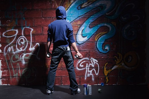 Teenager with cans of spray paint : Stock Photo