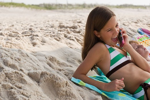 Girl at beach on cell phone : Stock Photo