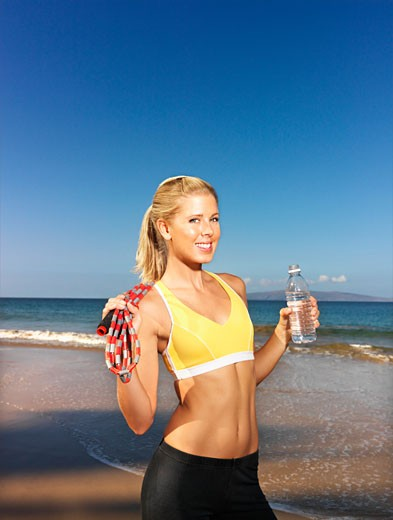 Woman posing with bottled water and jump rope : Stock Photo