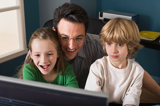 Father and children using computer : Stock Photo