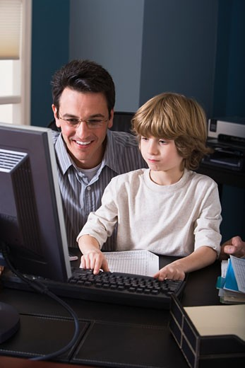 Stock Photo: 1557R-309766 Father and son using computer