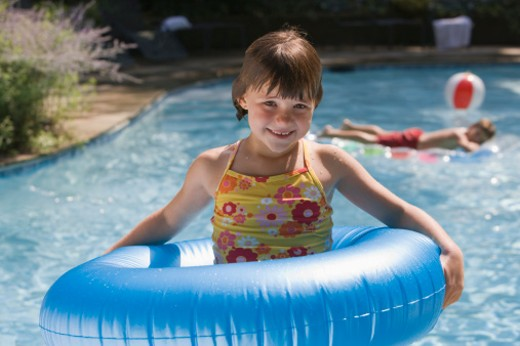 Girl in flotation device in pool : Stock Photo