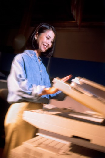 Businesswoman using copy machine : Stock Photo