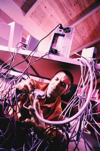 Stock Photo: 1557R-312900 Man with tangled computer cables