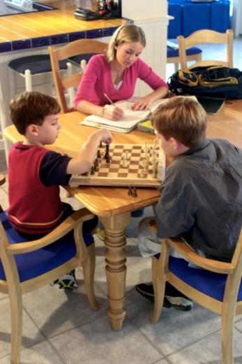Stock Photo: 1557R-313171 Teenage girl doing homework while brothers play chess