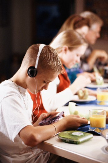 Stock Photo: 1557R-313406 Teenage boy listening to headphones at breakfast table