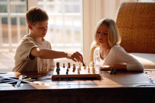 Boy and girl playing chess : Stock Photo