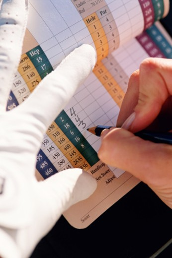 Hands writing on golf score card : Stock Photo