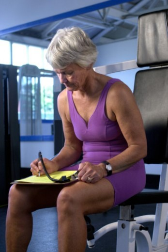 Woman with clipboard in gym : Stock Photo