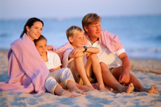 Family sitting on beach gazing at sunset : Stock Photo