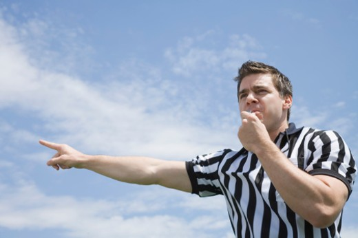 Referee blowing whistle and pointing : Stock Photo