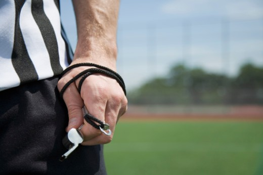 Referee's hand holding whistle : Stock Photo
